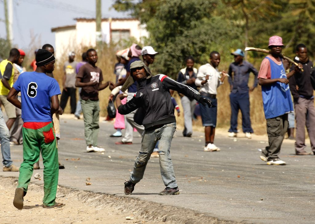 HARARE, July 4, 2016 - A protester hurls stones towards police during a protest in the impoverished suburb of Epworth on the outskirts of Harare, Zimbabwe, July 4, 2016. Zimbabwean police said they ...