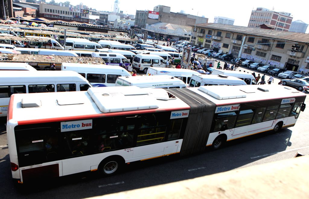 A Mercede-Benz passenger bus parks at a downtown bus terminal dominated by smaller commuter mini buses in Harare, Zimbabwe, July 8, 2014. Zimbabwe's Transport ... - Obert Mpofu