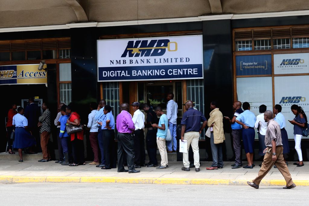 HARARE, Nov. 12, 2019 - People wait in a queue to withdraw the new bank notes at a bank in Harare, Zimbabwe, Nov. 12, 2019. Zimbabwean banks on Tuesday started to dispense new bank notes and coins ...