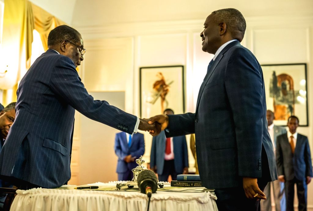 HARARE, Oct. 10, 2017 - Zimbabwean President Robert Mugabe (L, Front) congratulates Happyton Bonyongwe (R, Front) after he was sworn in as new Justice Minister at the State House in Harare, Zimbabwe, ...