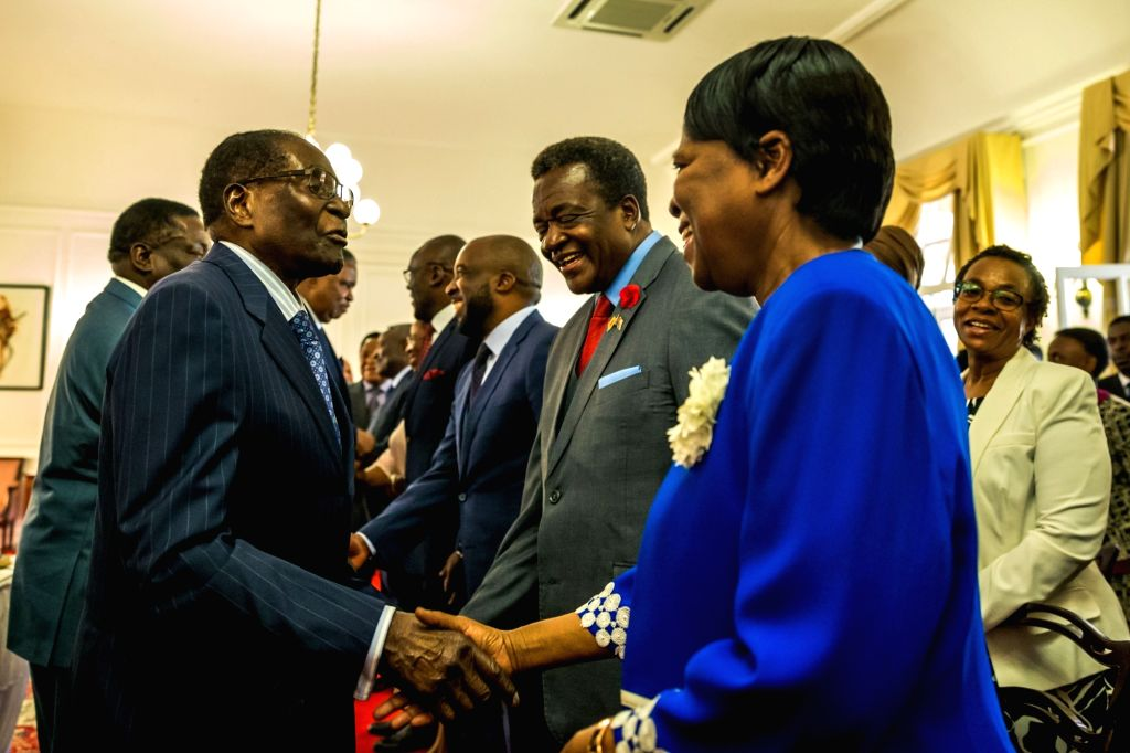 HARARE, Oct. 10, 2017 - Zimbabwean President Robert Mugabe (L, Front) congratulates Thokozile Mathuthu (R, Front) after she was sworn in as new Minister of State for Matabeleland North at the State ...