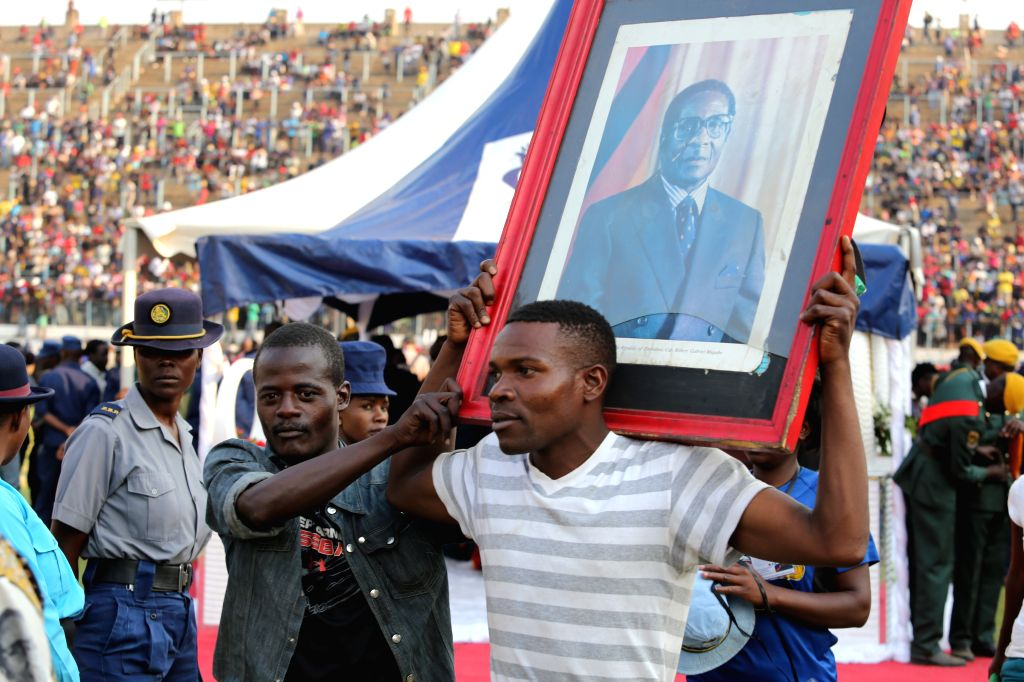 HARARE, Sept. 12, 2019 - A man holding the late former Zimbabwean President Robert Mugabe's portrait leaves after paying respect to Mugabe in Harare, Zimbabwe, on Sept. 12, 2019. Thousands of ...