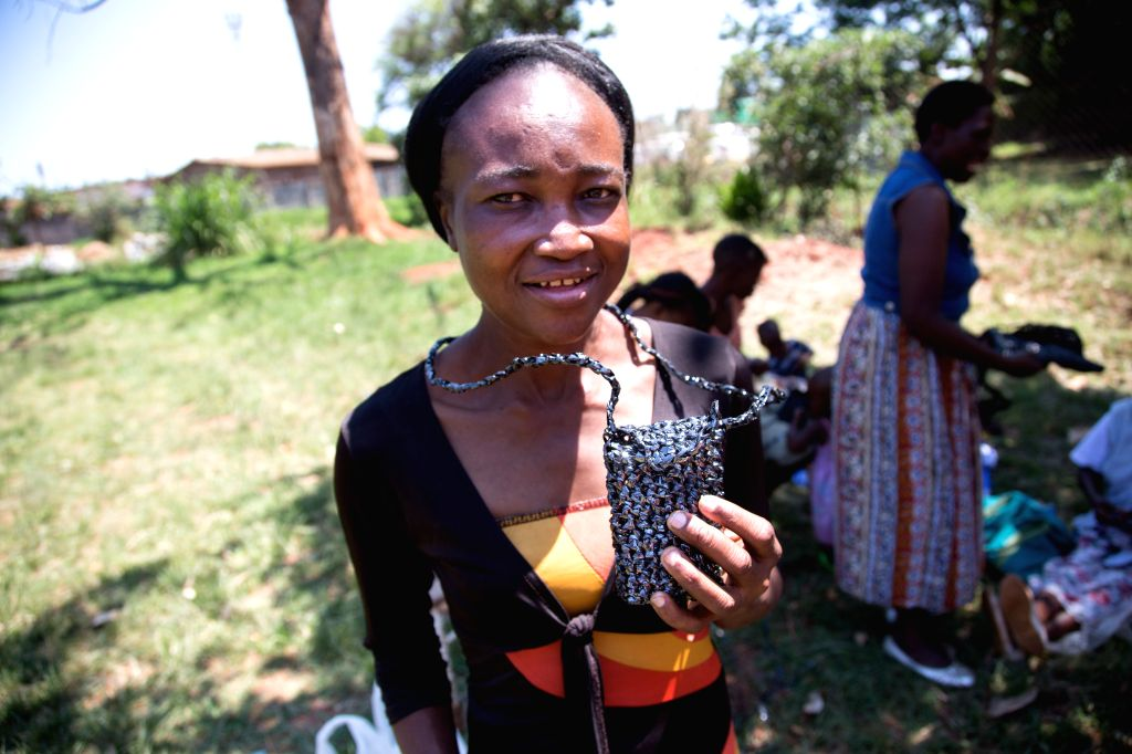 Harare (Zimbabwe): Farai Chinhoyi shows a cellphone pouch made out of recycled plastic at a workshop in Warren Park Polyclinic, southern suburbs of Harare, Zimbabwe, November 28, 2014. Chinhoyi is a .