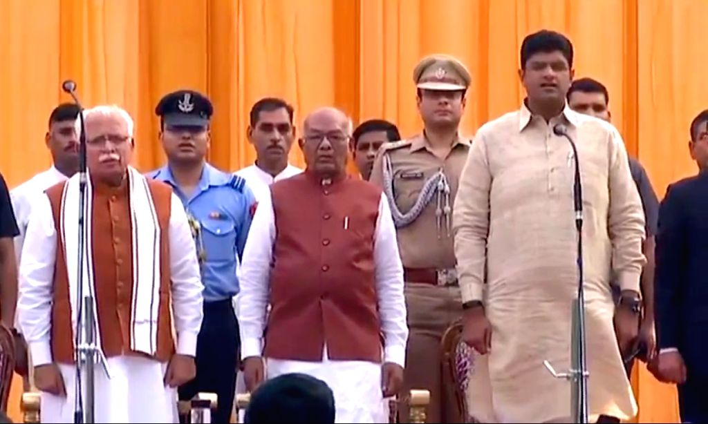 Harayana Governor Satyadeo Narain Arya, Chief Minister Manohar Lal Khattar and Deputy Chief Minister Dushyant Chautala stand for the national anthem during the swearing-in ceremony at the ... - Manohar Lal Khattar