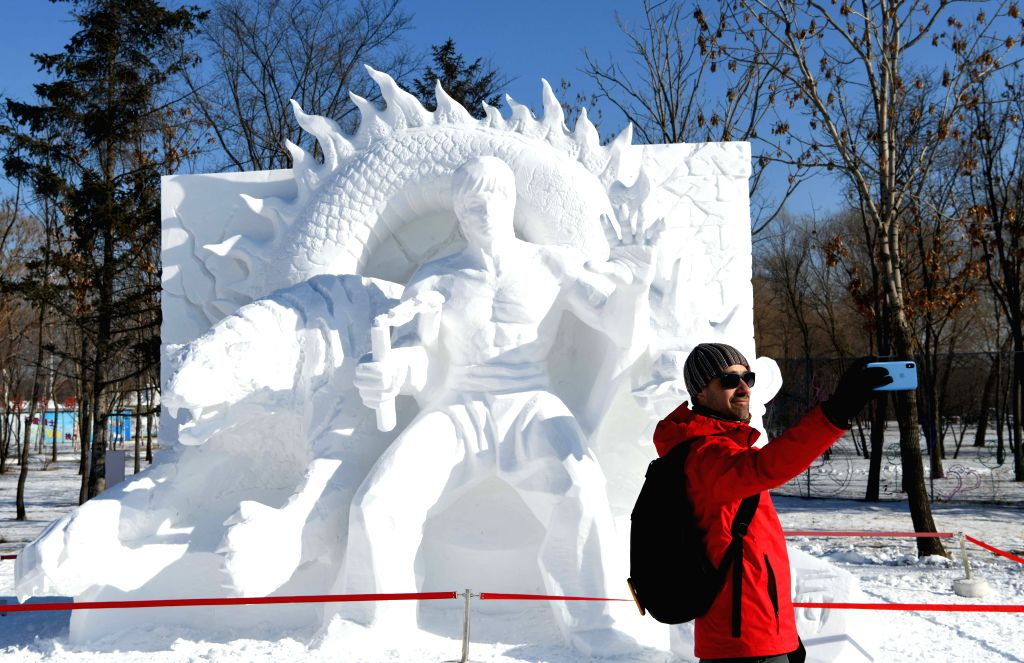 HARBIN, Jan. 26, 2019 - A tourist takes selfie with snow sculpture work at the Sun Island first international art elite snow sculpture competition in the Sun Island International Snow Sculpture Art ...