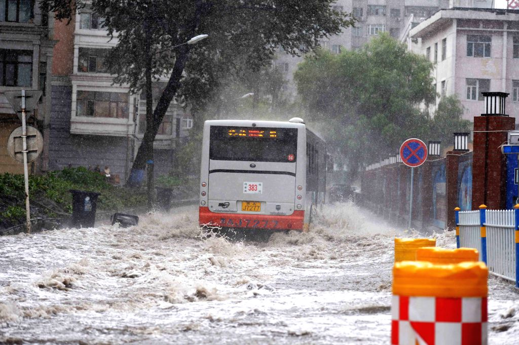 HARBIN, July 31, 2016 - A bus runs on a waterlogged road in Harbin, northeast China's Heilongjiang Province, July 31, 2016. Torrential rain hit the city on Sunday, causing severe waterlogging in some ...