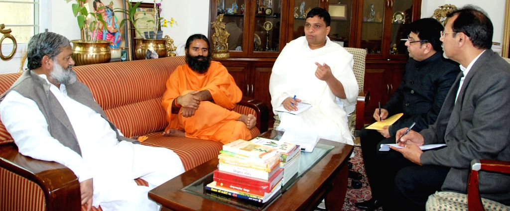Haryana Health Minister Anil Vij calls on yoga guru Ramdev at Patanjali Yogpeeth in Haridwar on Jan 15, 2015. Also seen Acharya Balkrishna. - Anil Vij