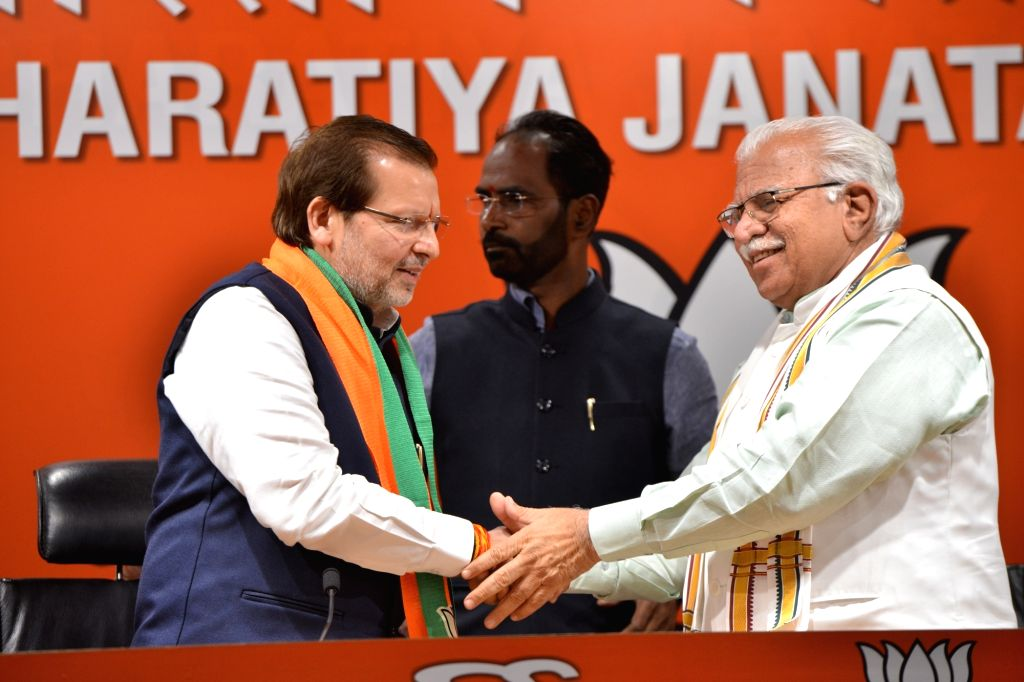 Haryana Chief Minister and BJP leader Manohar Lal Khattar welcomes Congress MP Arvind Sharma into the party in New Delhi, on March 15, 2019. - Manohar Lal Khattar and Arvind Sharma
