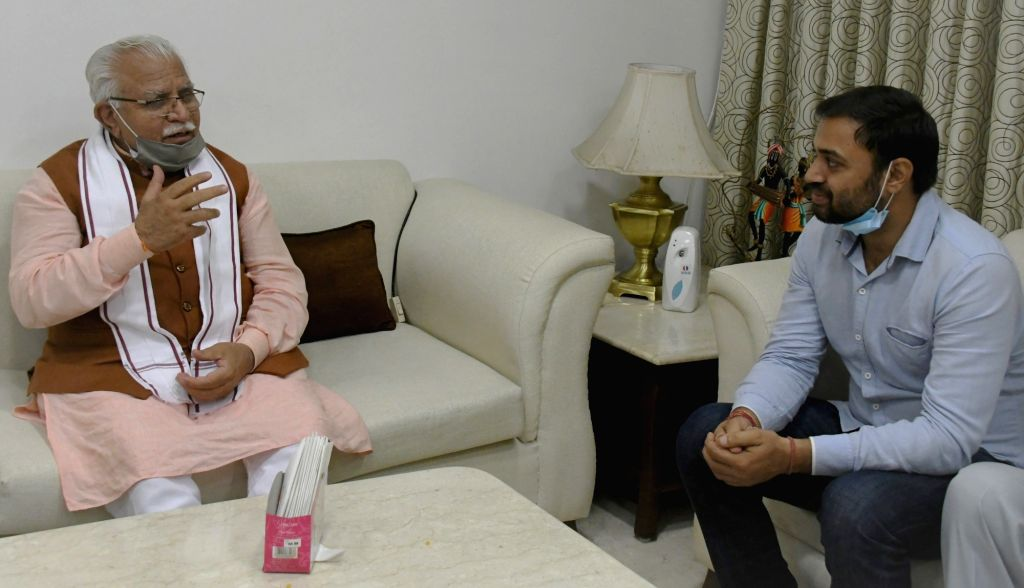 Haryana Chief Minister Manohar Lal interacting with Pradeep Singh Malik from Sonipat, who topped the UPSC Civil Services Examination, 2019, in New Delhi on August 9, 2020. - Manohar Lal and Pradeep Singh Malik