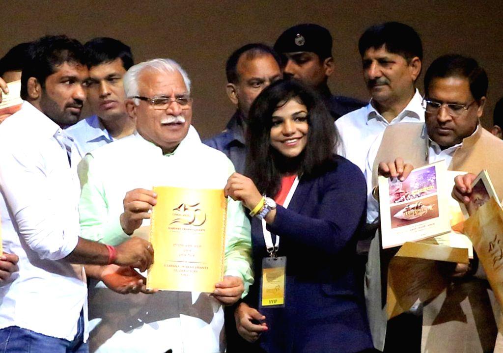 Haryana Chief Minister Manohar Lal Khattar with Olympic Medalists Yogeshwar Dutt and Sakshi Malik unveil the logo of Haryana Swarna Jayanti Utsav in Gurgaon on Sept 17, 2016. - Manohar Lal Khattar, Malik and Medalists Yogeshwar Dutt