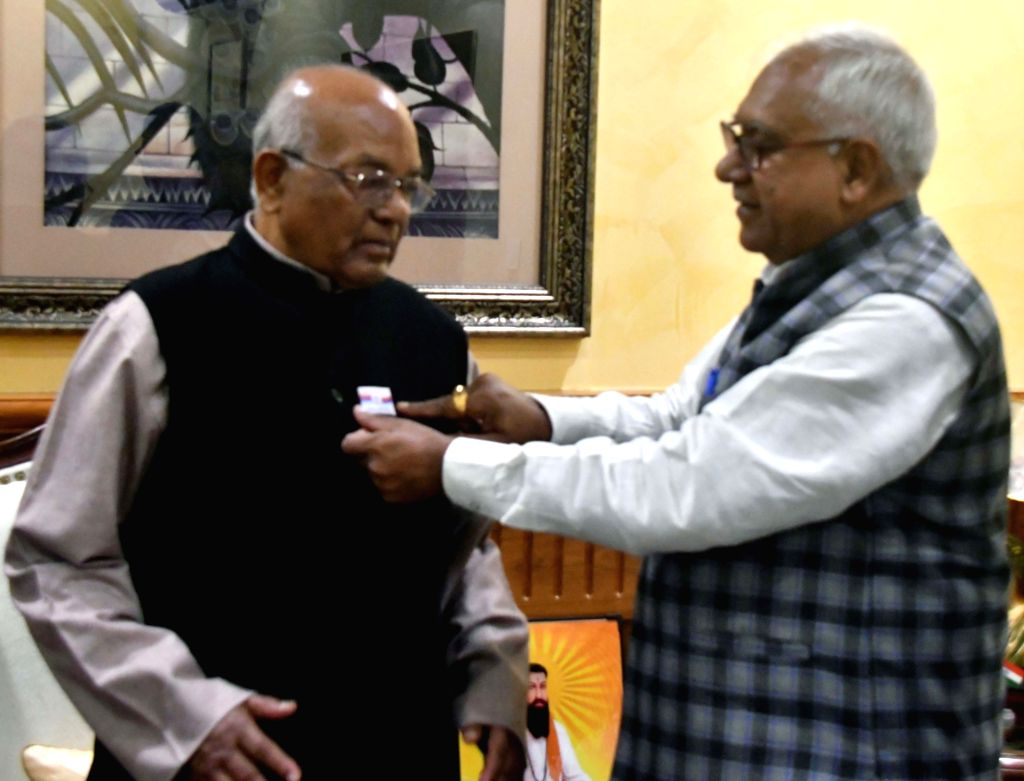 Haryana Governor Satyadeo Narain Arya being pinned with a flag sticker by Minister of State for Sainik and Ardh Sainik Welfare Om Prakash Yadav on the eve of  Armed Forces Flag Day, in ... - Prakash Yadav