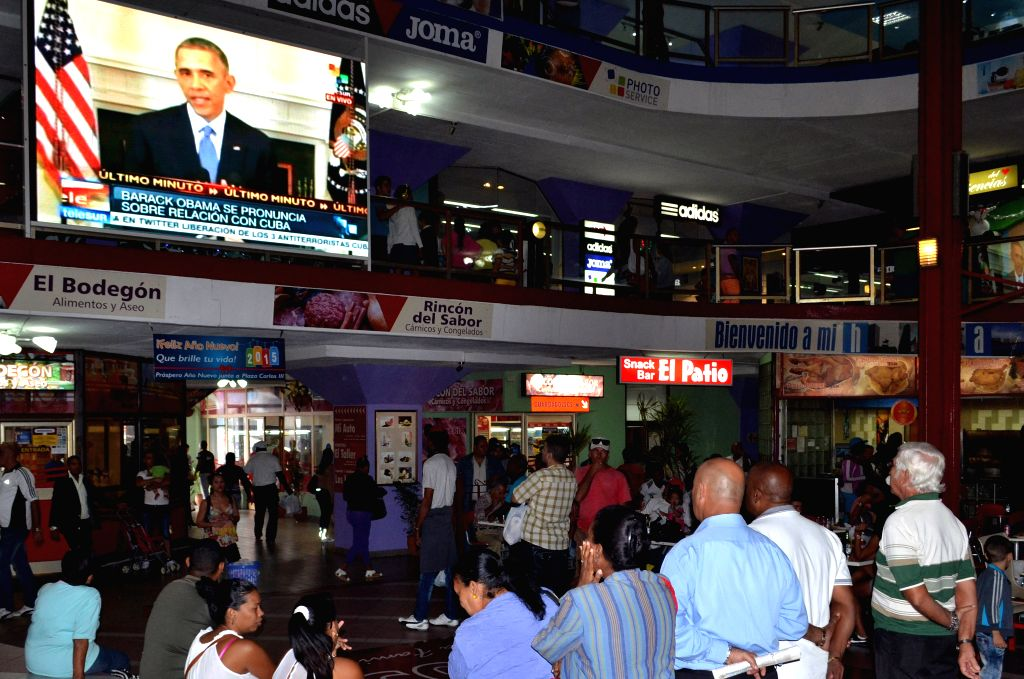 Residents listen to a televised speech by U.S. President Barack Obama, in Havana, capital of Cuba, on Dec. 17, 2014. Cuban leader Raul Castro confirmed here ...