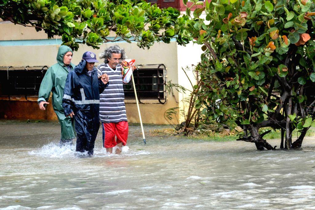 HAVANA, Sept. 11, 2017 - People walk through a flooded street after the passage of Hurricane Irma, in Havana, Cuba, on Sept. 10, 2017.