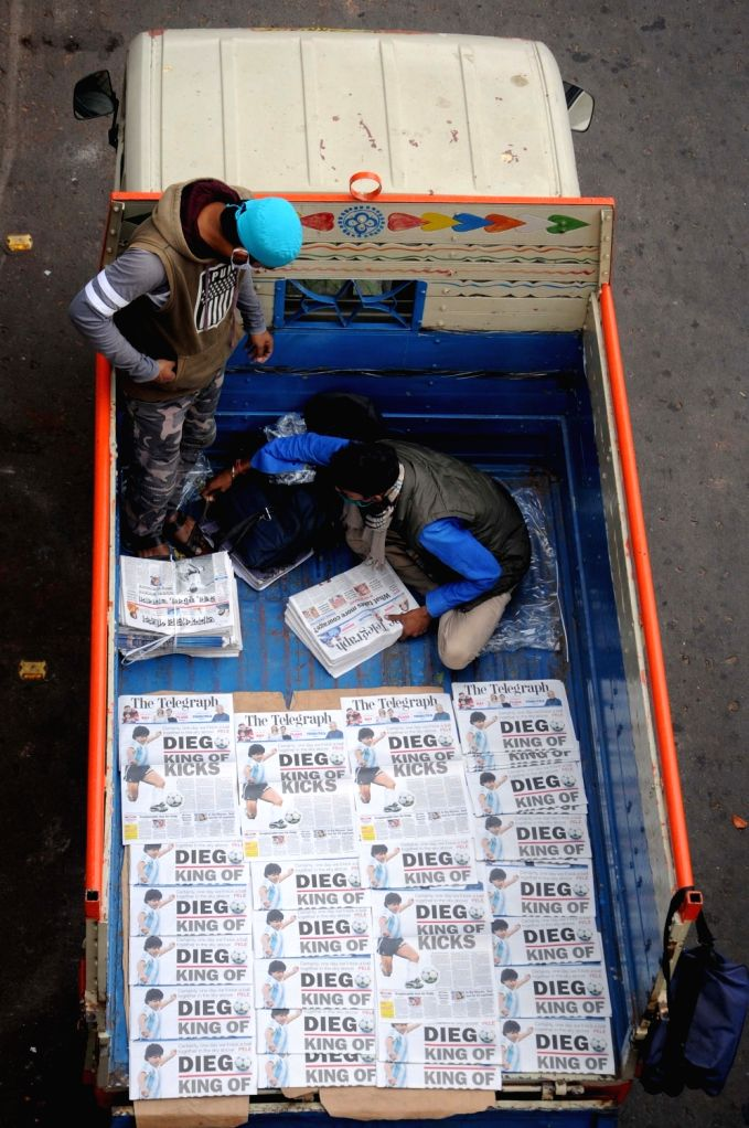 Hawkers selling newspapers which carry the news of the passing away of the legendary Argentinian footballer Diego Maradona, as the lead story, in Kolkata on Nov 26, 2020. The footballer ...