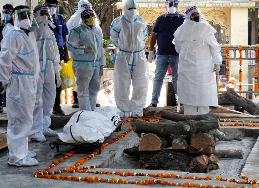 Health worker and relative carries the body of covid-19 affected victims for last rites at Nigambodh ghat in New Delhi on Saturday, 17th April, 2021.