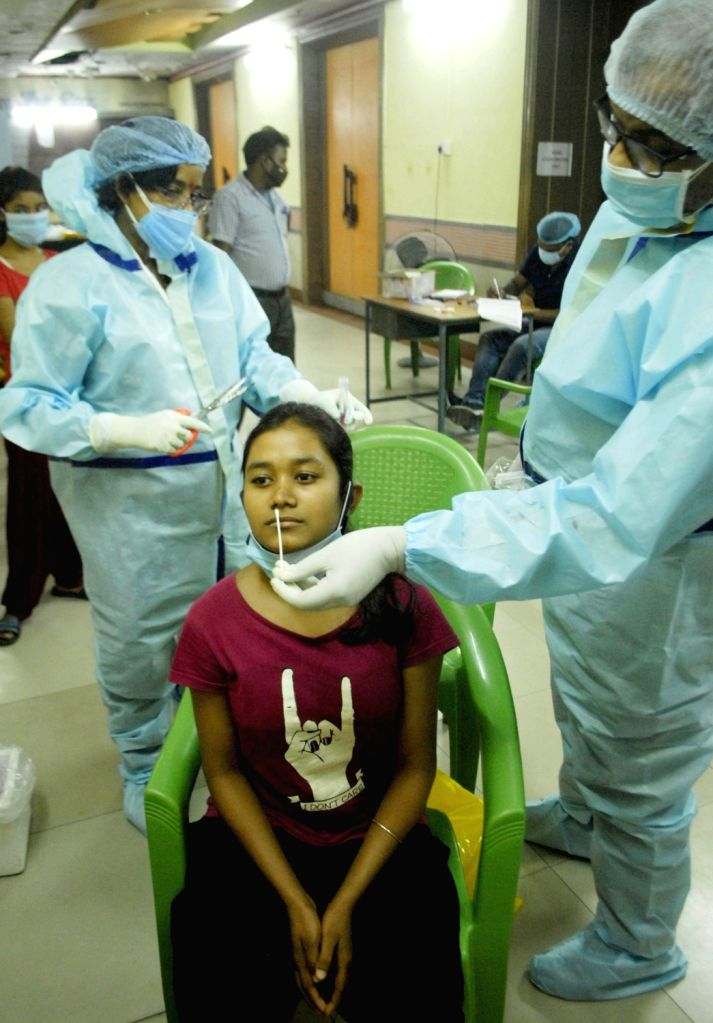 Health Worker collected swab from children for Covid test during increasing numbers of COVID 19 cases at Salt Lake in Kolkata 13 May, 2021.