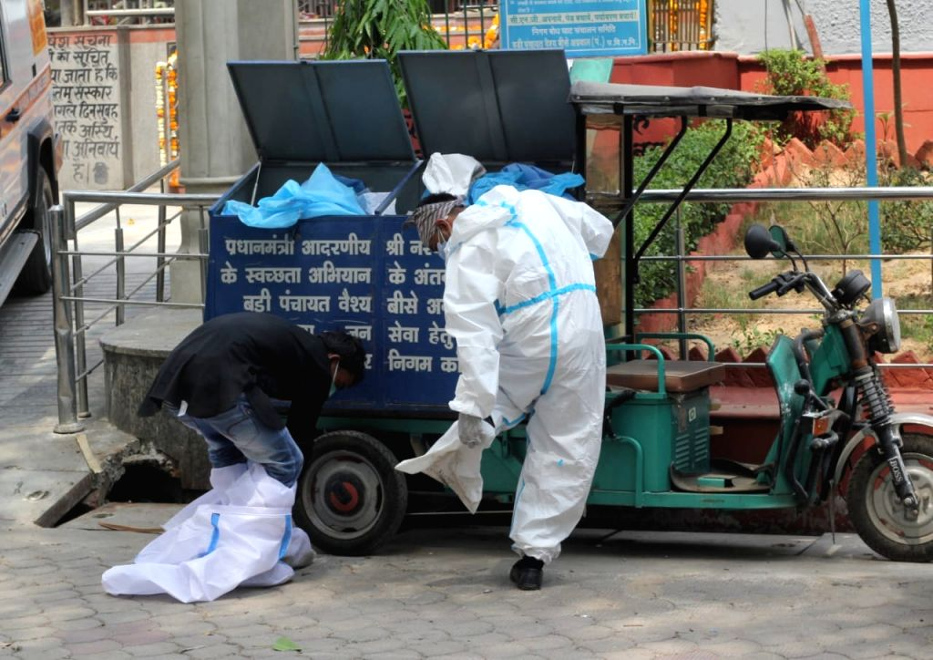 Health worker removing PPE suits after the covid-19 affected victims last rites at Nigambodh ghat in new Delhi on Friday April 16, 2021