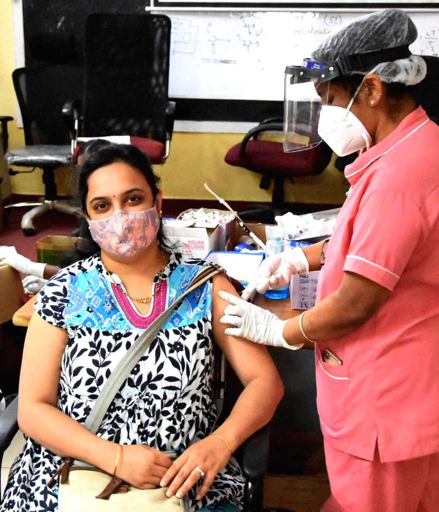 Health workers administering the COVID-19 vaccine to people during COVID-19 vaccination drive at KC General Hospital and some people waiting during COVID-19 vaccination drive in Bengaluru on Sunday ...