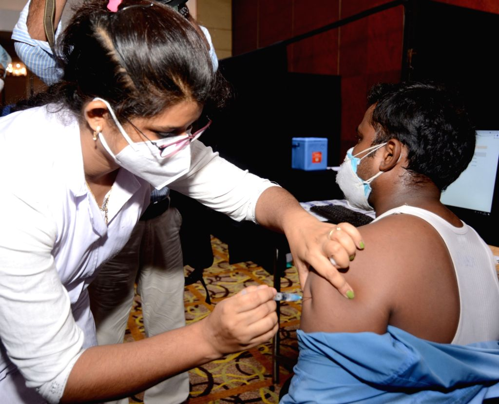 Health workers are giving the Covid - 19 vaccine to the employees and workers of the tourism and hospitality industry organised by the Government of West  Bengal in collaboration with ...