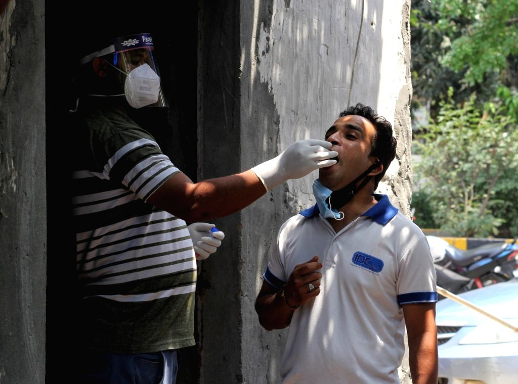 Health workers collect swab samples for Covid-19 testing at a testing center in New Delhi on Friday, May 07, 2021.