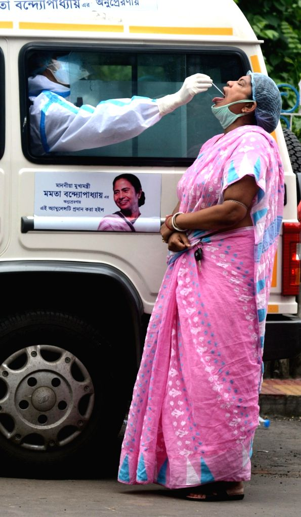 Health workers collect swab samples from people for COVID-19 testing, in Kolkata on July 3, 2020.