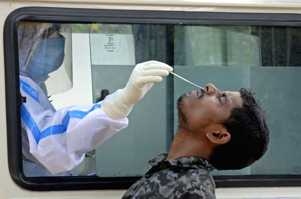 Health workers collect swab samples from people for COVID-19 testing, in Kolkata on July 4, 2020.
