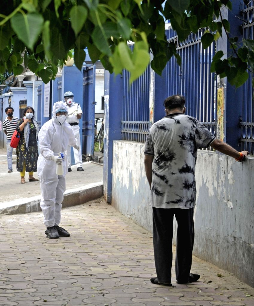 Health workers engaged in their duties wearing Personal Protective Equipment (PPE) suit sprays disinfectants at Kolkata's M R Bangur Hospital where a central vigilance team visited during ...