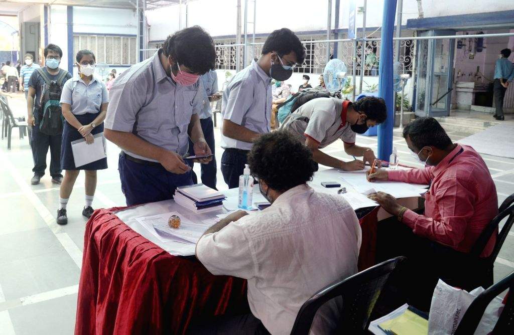 """Health workers inoculate COVID-19 vaccine to a student of class 12 during a vaccination drive for students and guardians at a private school """"South Point High School"""" in Kolkata on ..."""