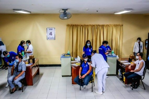 Health workers receive the COVID-19 vaccines from China's Sinovac on the first day of the vaccination at the Lung Center of the Philippines in Manila, the Philippines on March 1, 2021.