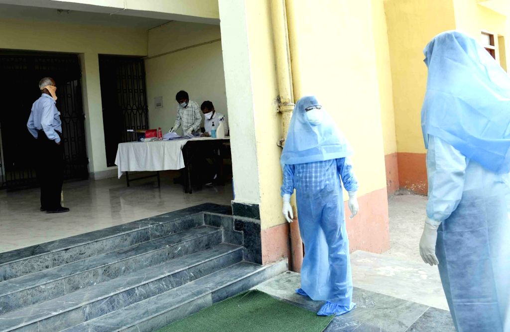 Health workers wearing Personal Protective Equipment (PPE) suits engaged in their duties at a Patna COVID-19 testing center during the extended nationwide lockdown imposed to mitigate the ...