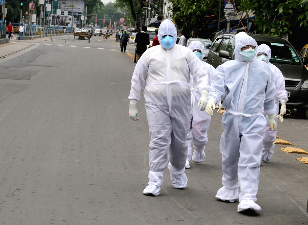 Health workers wearing Personal Protective Equipment (PE) suits walk past a deserted Kolkata street during the extended nationwide lockdown imposed to mitigate the spread of coronavirus; on ...