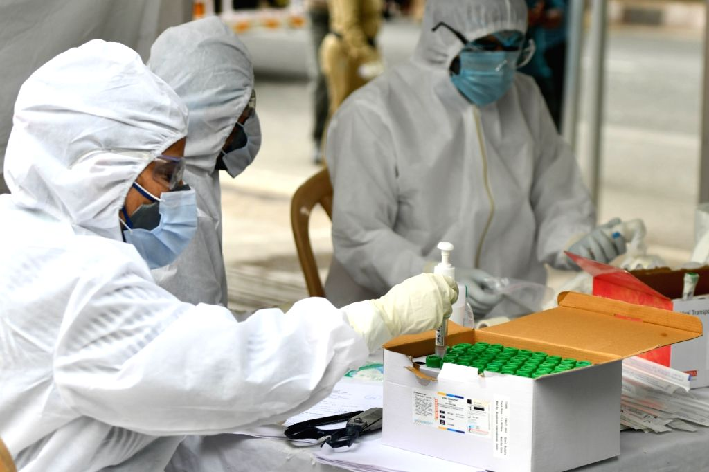 Health workers wearing Personal Protective Equipment (PPE) suits collect swab samples from people at a COVID-19 testing center in New Delhi during the extended nationwide lockdown imposed ...