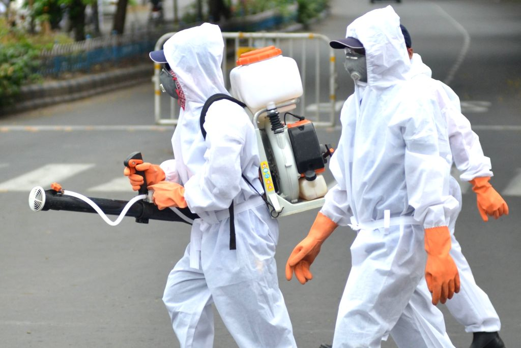 Health workers wearing Personal Protective Equipment (PPE) suits spray disinfectants during a sanitisation drive conducted across Kolkata during the extended nationwide lockdown imposed to ...