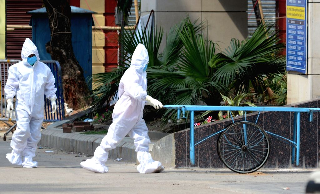 Health workers wearing Personal Protective Equipment (PPE) suits engaged in their duties at the Kolkata Medical College and Hospital that have been converted into a full- fledged COVID-19 ...