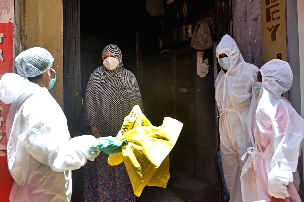 Health workers wearing Personal Protective Equipment (PPE) suits conduct COVID-19 screening at a Kolkata locality on June 25, 2020.