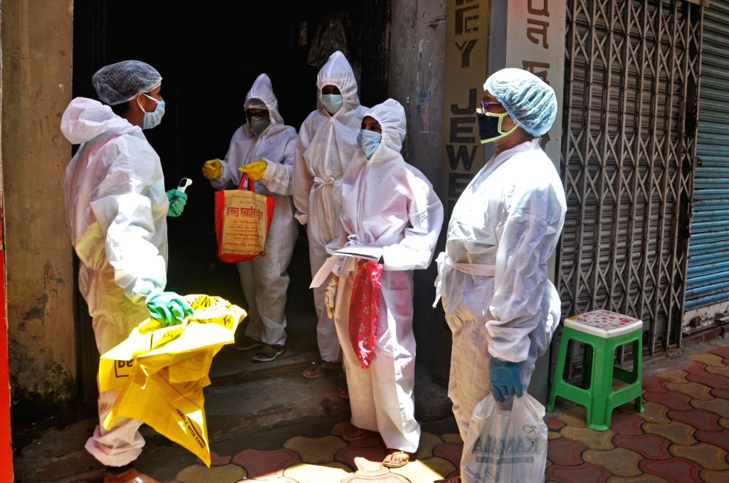 Health workers wearing Personal Protective Equipment (PPE) suits arrive to conduct COVID-19 screening at a Kolkata locality on June 25, 2020.