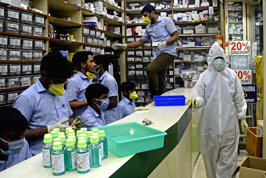 Health workers working at a medical store wear Personal Protective Equipment (PPE) suits as they engage in their duties in Kolkata during the extended nationwide lockdown imposed to mitigate ...