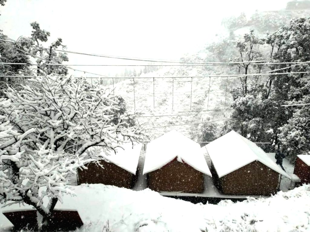 Heavy snowfall in Uttarkhand hills especially in Mussoorie-Dhanaulti severed road links on Friday as authorities closed schools after the Met forecast heavy rains. (Photo: IANS)
