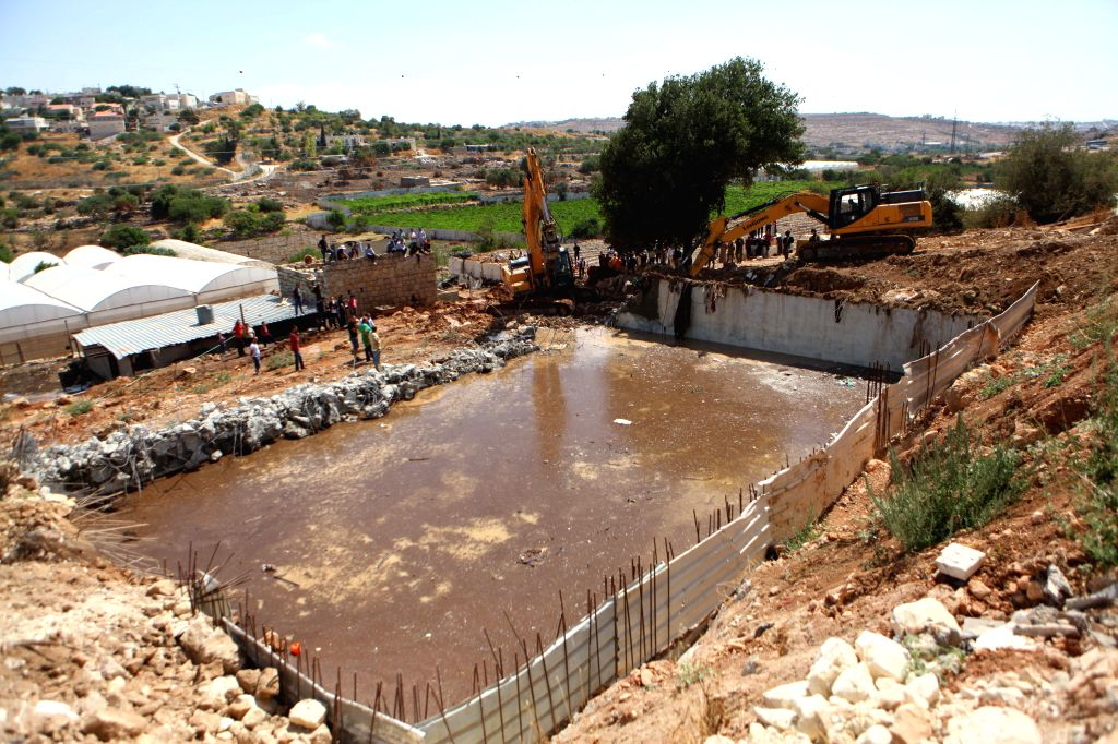 "HEBRON, July 16, 2019 - Israeli bulldozers demolish a water facility in ""Area C"" of the West Bank city of Hebron, July 16, 2019. The Israeli army demolished water wells and other facilities ..."
