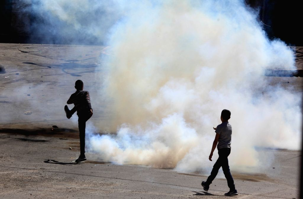 HEBRON, March 31, 2018 - A Palestinian protester tries to throw back a tear gas canister fired by Israeli soldiers during a clash in the West Bank city of Hebron, on March 31, 2018. The clash broke ...