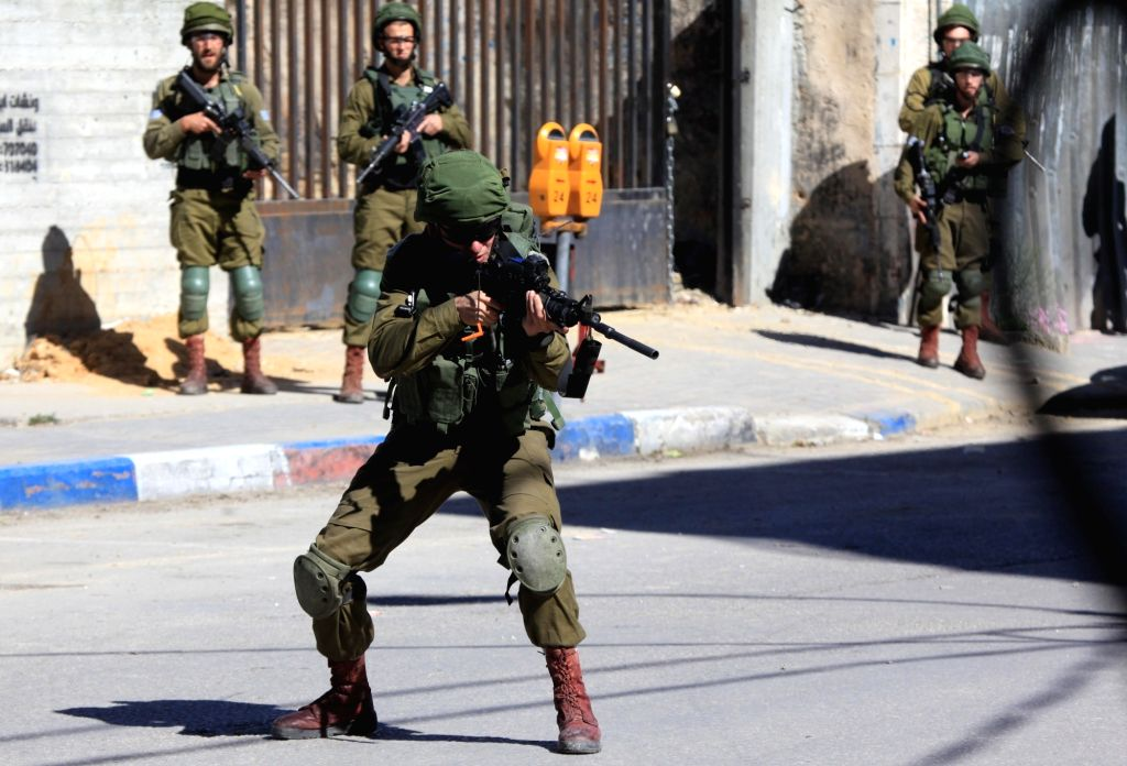 HEBRON, March 31, 2018 - Israeli soldiers take positions during a clash with Palestinian protesters in the West Bank city of Hebron, on March 31, 2018. The clash broke out after Friday that left some ...