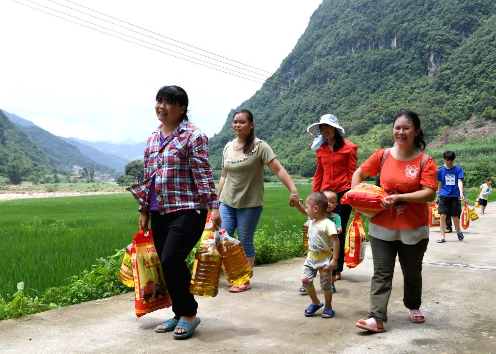 HECHI, July 17, 2019 - Villagers go back home with disaster relief materials in Pola Village of Aidong Township in Donglan County of Hechi, south China's Guangxi Zhuang Autonomous Region, July 16, ...