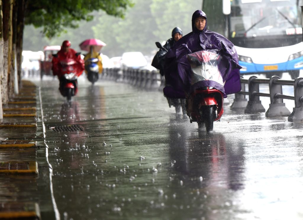 HEFEI, July 2, 2016 - Residents ride in rain in Hefei, capital of east China's Anhui Province, July 2, 2016. The local meteorological authority issued an orange alert for rainstorms Saturday morning.