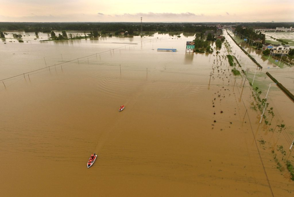 HEFEI, July 5, 2016 - Rescuers work on dinghies in flooded Shucheng County, east China's Anhui Province, July 3, 2016. Rainstorm has battered Shucheng County since June 30, ripping a breach on a dyke ...