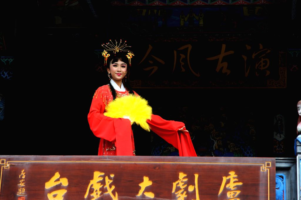 An actress performs Luju Opera, a traditional Chinese opera prevalent in Anhui, at a stage in Huiyuan of Hefei, capital of east China's Anhui Province, Sept. 6, 2014.