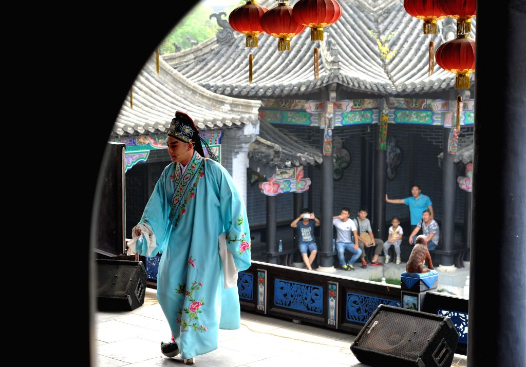 Audience watch an actor performing Luju Opera, a traditional Chinese opera prevalent in Anhui, at a stage in Huiyuan of Hefei, capital of east China's Anhui Province,