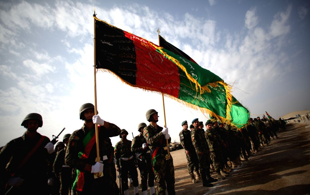 Afghan army soldiers hold the Afghan national flag during a ceremony marking the end of security transition from NATO-led troops to Afghan army in Gereshk district .