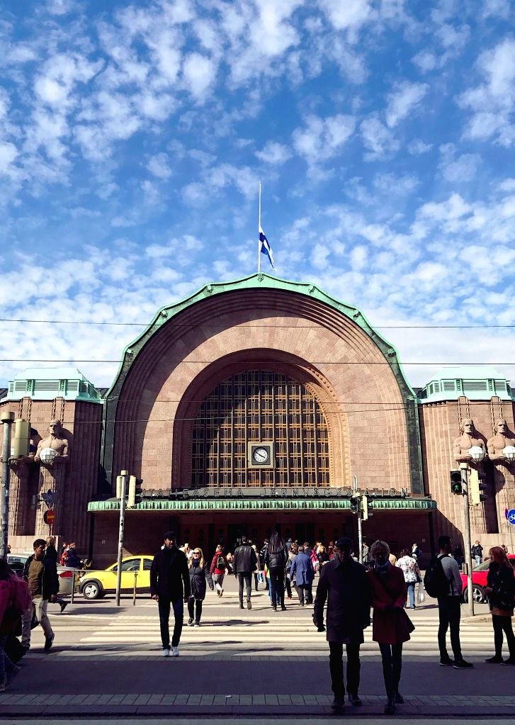 HELSINKI, May 13, 2017 - Pedestrians walk in front of Helsinki's central railway station where a Finnish national flag flies at half mast in Helsinki, Finland, on May 13, 2017, to mourn the former ...