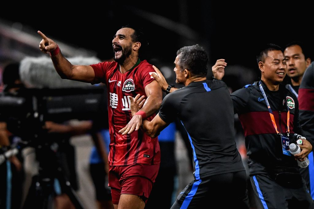 Henrique Dourado (1st L) of Henan Jianye FC celebrates after scoring during the second round match between Dalian Yifang FC and Henan Jianye FC at the postponed 2020 ...