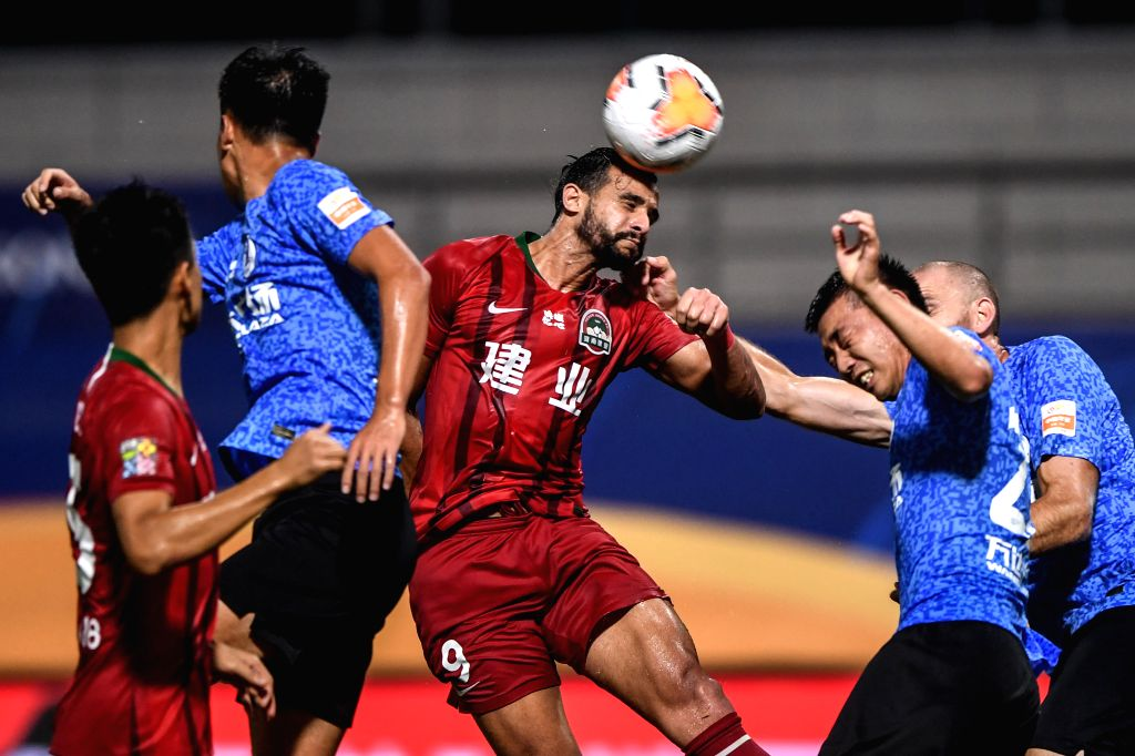 Henrique Dourado (C) of Henan Jianye FC heads for the ball during the second round match between Dalian Yifang FC and Henan Jianye FC at the postponed 2020 season ...
